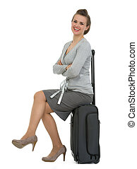 Smiling traveling woman sitting on suitcase