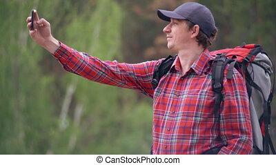 Smiling traveller in forest. - hiker taking selfie photo in...