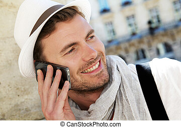 Smiling trendy guy talking on the phone in town