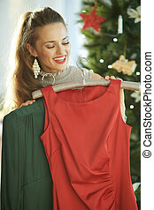 smiling trendy housewife selecting festive Christmas dresses