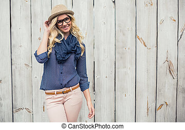 Smiling trendy model posing on wooden background