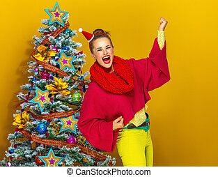 smiling trendy near Christmas tree woman rejoicing
