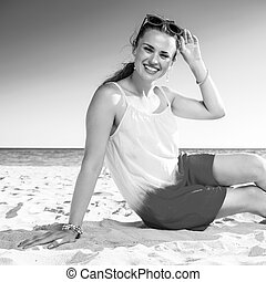 smiling trendy woman in colorful dress sitting on beach