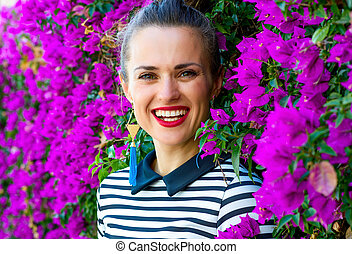 smiling trendy woman in front of colorful magenta flowers...