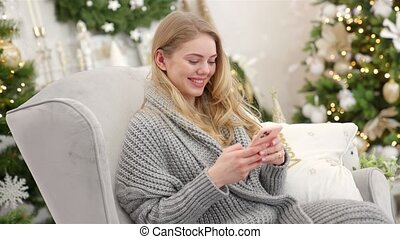 Smiling trendy woman in gray cozy sweater sittin on comfortable armchair and sending text message from her mobile phone near Christmas tree