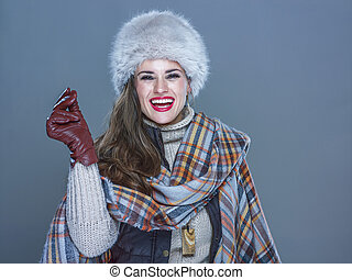 smiling trendy woman isolated on cold blue snapping fingers