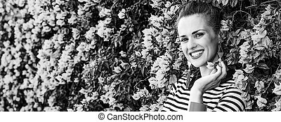 smiling trendy woman near colorful magenta flowers bed -...