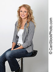 Smiling trendy woman sitting on white background