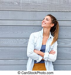 Smiling trendy woman standing with arms crossed