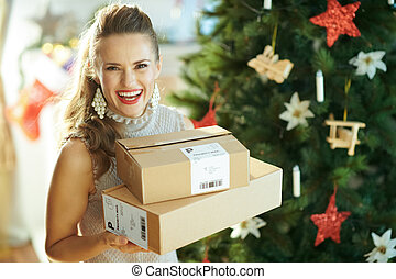 smiling trendy woman with parcels near Christmas tree