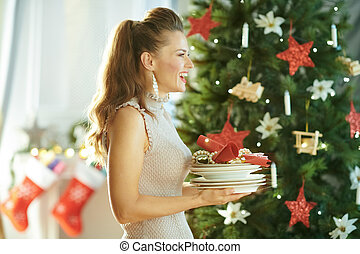 smiling trendy woman with serving plates near Christmas tree