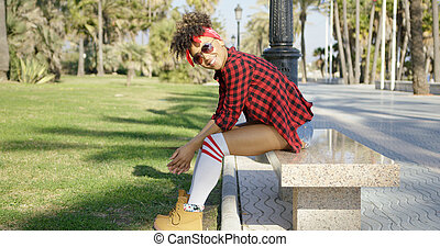 Smiling trendy young woman on a marble bench