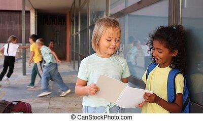 Two cute preteen schoolgirls talking friendly near school building during break between lessons on warm autumn day