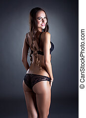 Smiling underwear model posing back to camera
