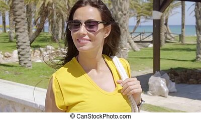 Smiling vivacious young woman in sunglasses