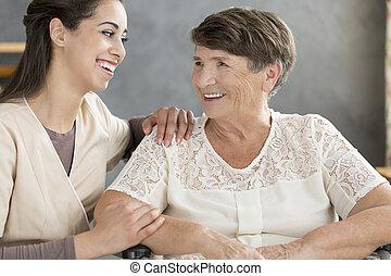 Smiling volunteer and elderly woman