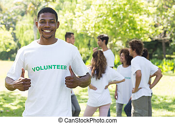 Smiling volunteer showing thumbs up - Portrait of smiling...