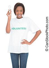 Smiling volunteer woman holding light bulb