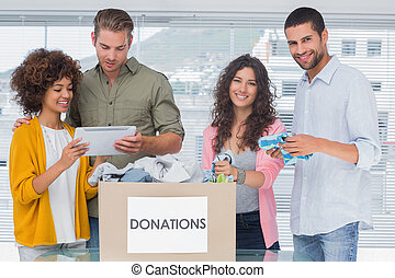 Smiling volunteers using tablet and taking out clothes from donations for a charity