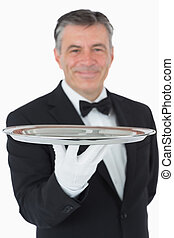 Smiling waiter holding a silver tray