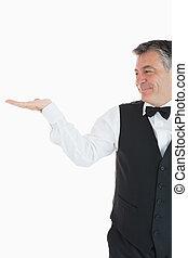 Smiling waiter holding something