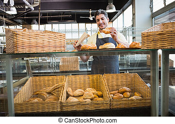 Smiling waiter in apron choosing bread