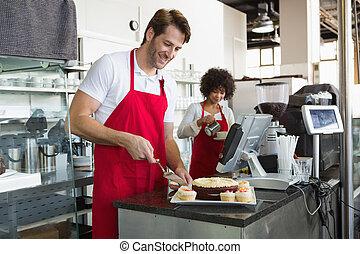 Smiling waiter slicing cake
