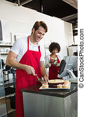 Smiling waiter slicing cake with waitress behind him