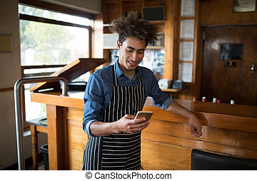 Smiling waiter using mobile phone at counter