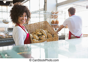 Smiling waitress carrying basket of bread