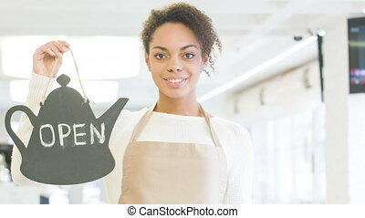 Smiling waitress holding an opening sign. - We are open....