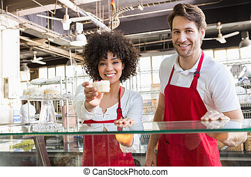 Smiling waitress in red apron offering cupcake
