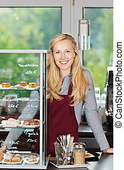 smiling waitress leaning on coffee shop counter - friendly...
