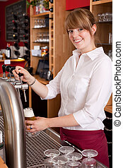 Smiling waitress pouring draft beer from a metal spigot on...