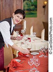 smiling waitress setting the table