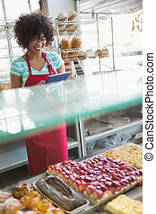 Smiling waitress using tablet pc