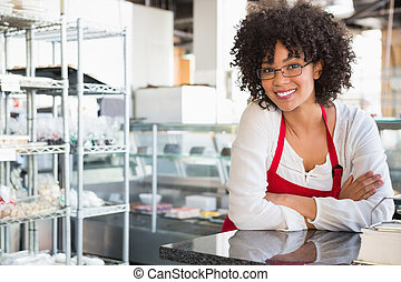 Smiling waitress with glasses leaning on counter at the ...