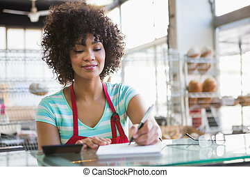 Smiling waitress writing on notepad at the bakery