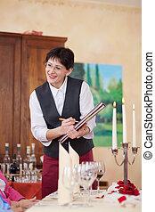 smiling waitress writing the order