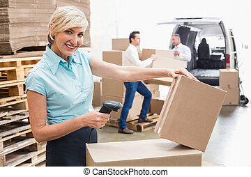 Smiling warehouse manager scanning package in warehouse