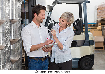 Smiling warehouse managers working on clipboard