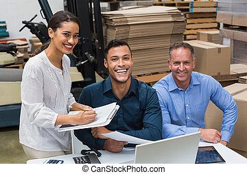 Smiling warehouse managers working together in a large...