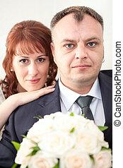 Smiling wedding couple looking at camera