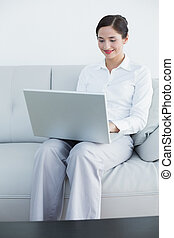 Smiling well dressed woman using laptop on sofa