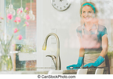 Smiling wife cleans counter top in the kitchen with clock on...