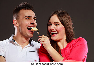 Smiling wife feeding happy husband with banana.