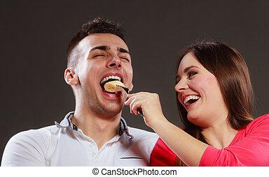 Smiling wife feeding happy husband with banana.