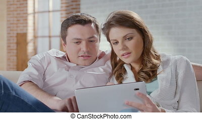 Smiling wife husband shopping online, choosing items on tablet