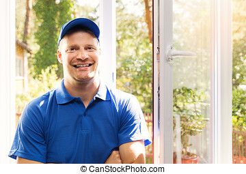 smiling window installer in blue uniform standing in the room