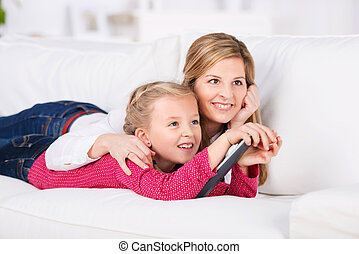 Smiling Woman And Girl With Remote Control On Sofa